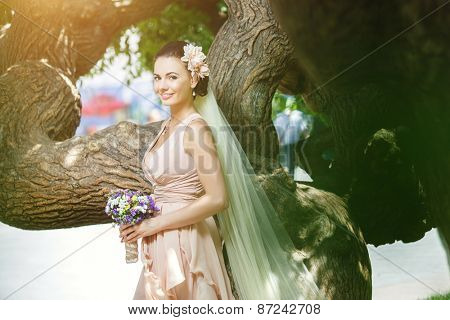 beautiful happy bride in beige dress smiling standing among green trees in sunlight