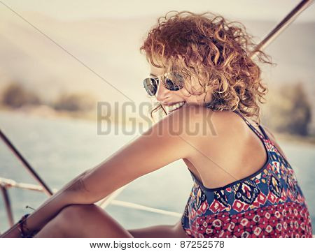 Portrait of beautiful happy woman with stylish hairdo having fun on sailboat, enjoying mild sunset light, funky style, active summer vacation