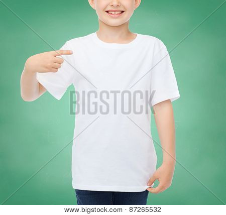 school, education, advertising, people and childhood concept - smiling little boy in white blank t-shirt pointing finger at himself over green chalk board background