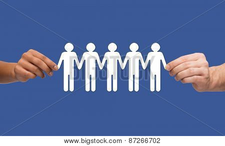community, unity and teamwork concept - multiracial couple hands holding paper chain people over blue background