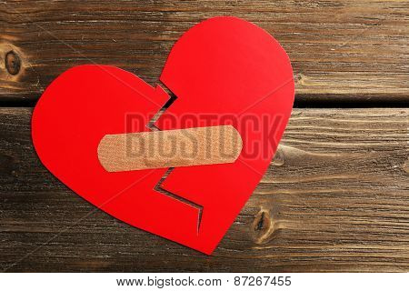 Broken heart with plaster on wooden background