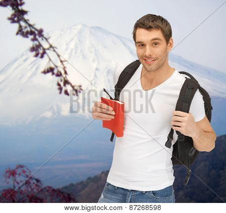 people, travel, tourism and education concept - happy young man with backpack and book travelling over japan mountains background poster