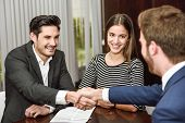 Smiling young couple shaking hands with an insurance agent or investment adviser poster