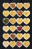 Large pasta food selection in heart shaped porcelain dishes over dark wood background. Titles provided. poster