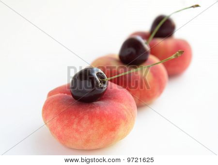 Peaches and cherries on white background