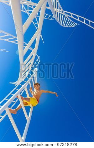 young happy kid - boy - climbing white ladders going nowhere up on natural sky background, outdoor