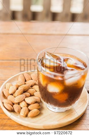 Glass Of Black Iced Coffee With Almond Grain