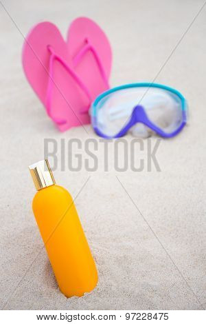 Skin Care Concept - Close Up Of Suntan Lotion Bottle, Diving Mask And Flip Flops On Sandy Beach