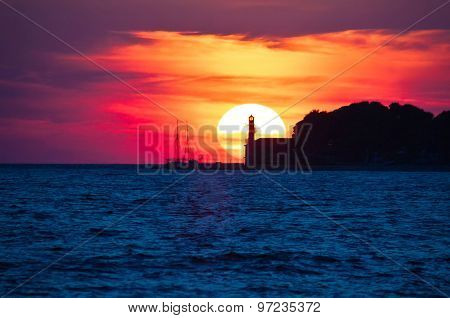 Epic Sunset View With Lighthouse And Saiboat