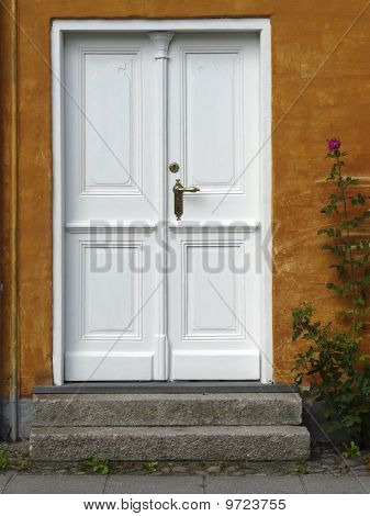 Front Door With A Rosebush In The Historic Old Town Of Christiansfeld In Denmark