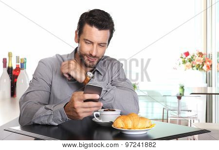 Coffee Break, Handsome Man Use The Smart Phone At The Bar With Cappucino And Croissant On The Table