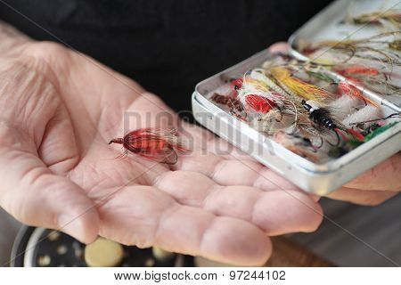 Artificial fishing flies in box and on hand