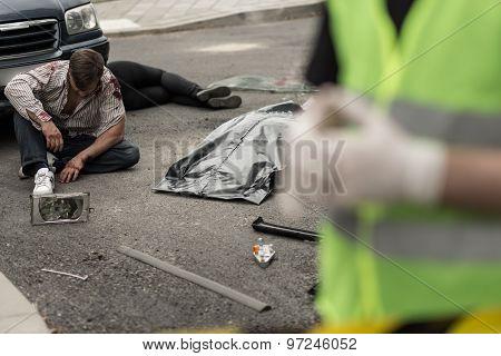 Injured man sitting on the street after car crash poster