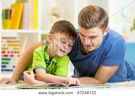 Father and son read together sitting on the floor. Kid boy reading story book with his dad at home. poster