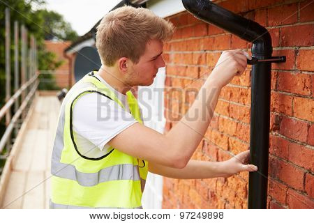 Construction Worker On Scaffolding Fixing Drain Pipe