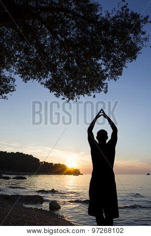 Man On Coast Saluting Sun