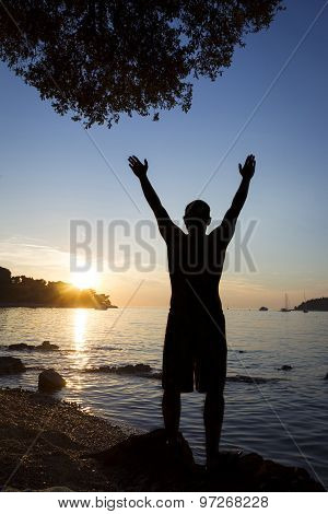 Man Saluting Sun On Shore