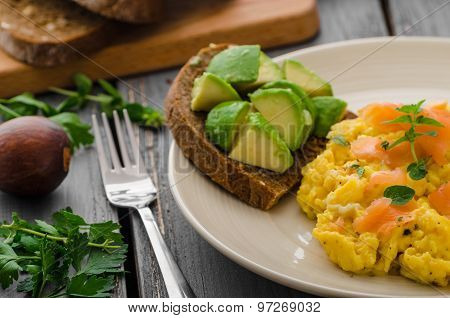Scrambled eggs with smoked salmon and whole wheat toast with avocado and lemon poster