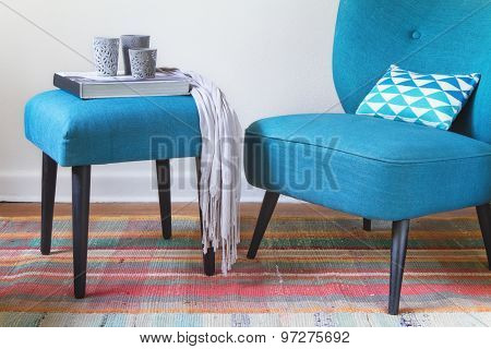 Teal fabric armchair and ottoman with home wares