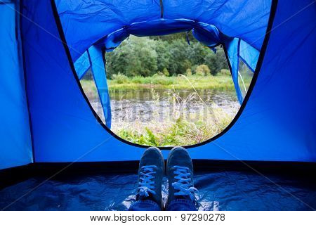 camping, travel, tourism, hike and people concept - close up of camper legs lying near blur tent entrance and enjoying natural landscape