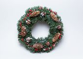 Christmas wreath of fir branches decorated with ilex, cypress cones, pine cones and artificial snow on white background. poster