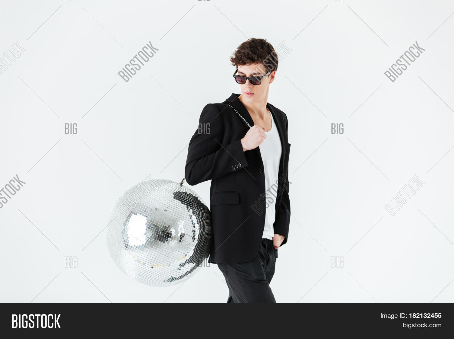 Side view of a man in suit and sunglasses carrying disco ball over white background