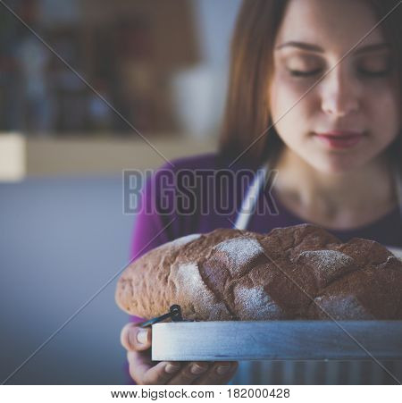 Young woman holding tasty fresh bread in her kitchen .