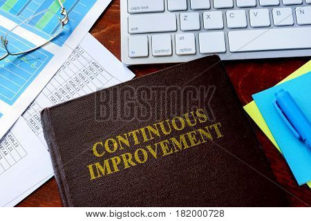 Book with title continuous improvement on a table.