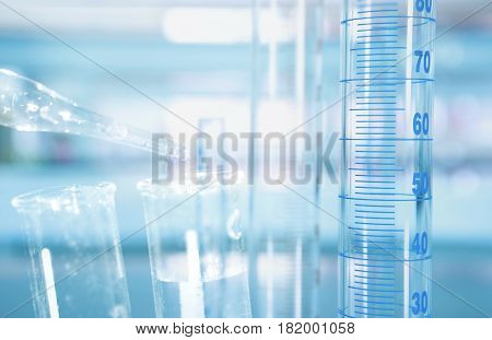 cylinder with scale and test tube water drop with science laboratory blue background