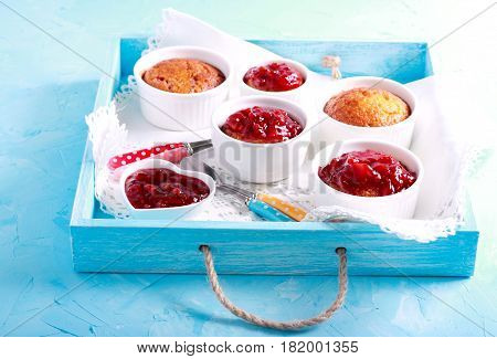 Coconut and raspberry puddings in ramekins on tray