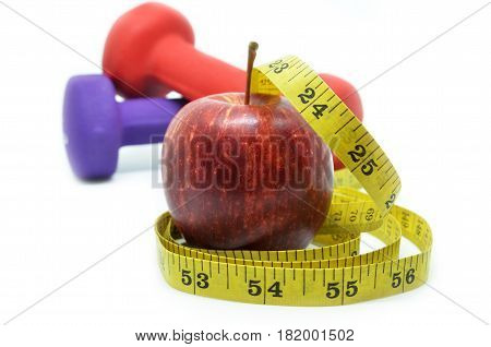 Dumbbell with measuring tape and red apple. Health concept