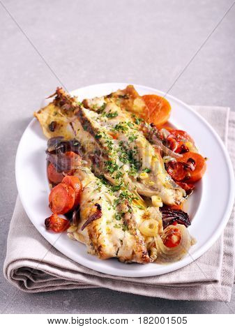 Grey mullet baked with vegetables on plate