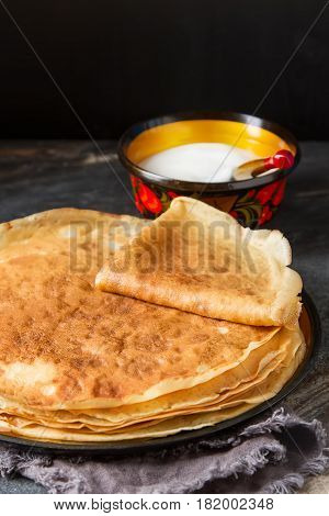 Stack Of Pancakes On A Wooden Plate With Sour Cream. Traditional