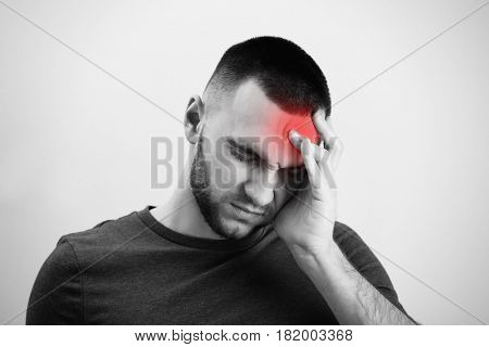 Young man suffering from headache on light background