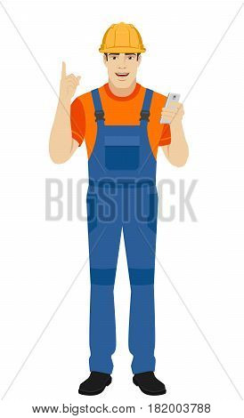 Builder with mobile phone and pointing up. Full length portrait of builder in a flat style. Vector illustration.