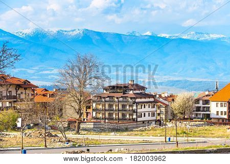 Bansko, Bulgaria spring view with trees, mountains peaks landscape and houses