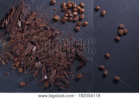 Dark chopping chocolate black roasted coffee beans on slate board over black textural background. Chocolate dessert confectionery and sweets concept