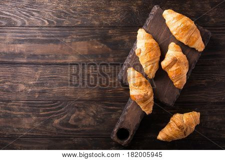 Delicious fresh mini croissants on wooden cutting board on old dark background. Healthy Breakfast with copy space. Top view.
