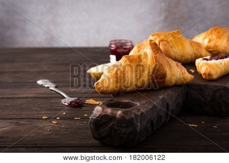 Delicious fresh mini croissants with fruit jam on wooden cutting board on old dark background. Healthy Breakfast with copy space.