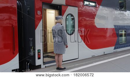 ST. PETERSBURG, RUSSIA - MAY 28, 2016: Train conductor at the double-decker train Mikhail Ulyanov in the day of its first departure from St. Petersburg to Adler