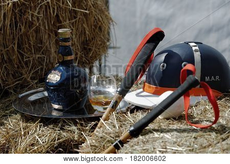 TSELEEVO, MOSCOW REGION, RUSSIA - JULY 26, 2014: Equestrian helmet, polo mallets, and a bottle of Scotch whiskey on the bales of hay during the British Polo Day