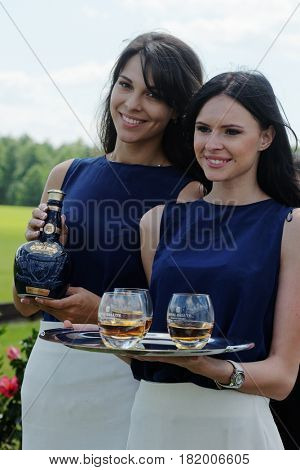 TSELEEVO, MOSCOW REGION, RUSSIA - JULY 26, 2014: Girls offer Royal Salute whiskey to the guests of British Polo Day. It was the second British Polo Day in Russia