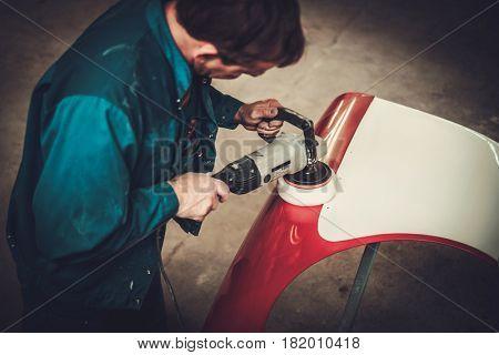 Mechanic polishning car body details in restoration workshop
