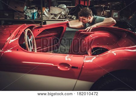Mechanic working on car body details in restoration workshop