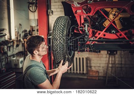 Mechanic working on classic car wheels and suspension in restoration workshop