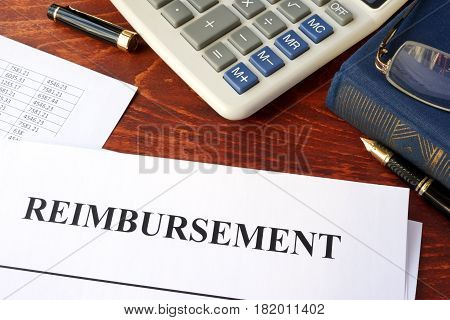 Document with title reimbursement on a table.
