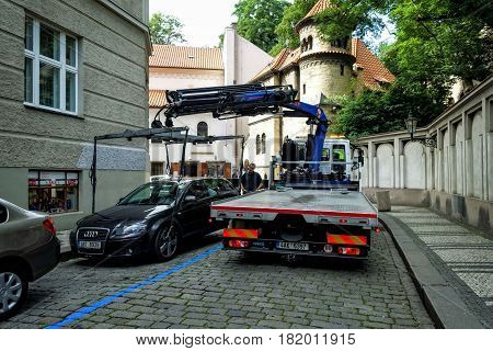 Prague, Czech Republic - June 25, 2016: Tow truck from the street evacuated incorrectly parked car.