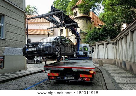 Prague, Czech Republic - Juny 25, 2016: Tow truck from the street evacuated incorrectly parked car.