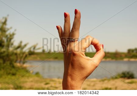 Woman hand showing okay sign gesture against the backdrop of summer lake
