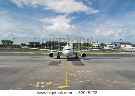White passenger plane takes off from the airport runway. Airplane front view.